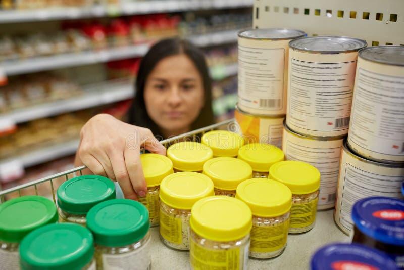 Γυναίκα που παίρνει το βάζο με τα τρόφιμα από το ράφι στο παντοπωλείο στοκ εικόνα