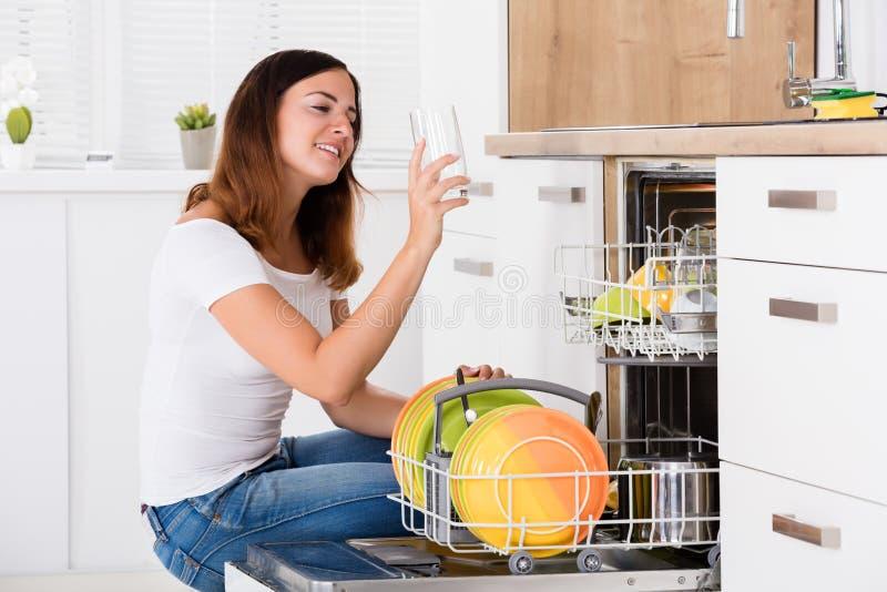 Γυναίκα που παίρνει το γυαλί κατανάλωσης από το πλυντήριο πιάτων στοκ φωτογραφία με δικαίωμα ελεύθερης χρήσης