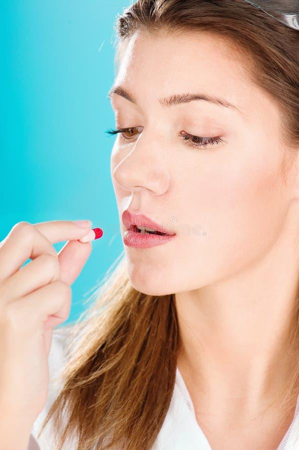Γυναίκα που παίρνει το κόκκινο χάπι στοκ φωτογραφία