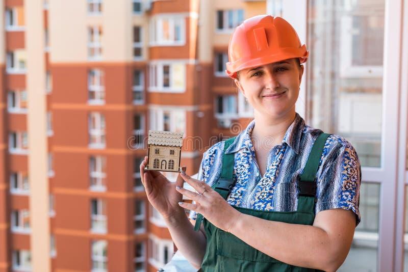 Γυναίκα που παρουσιάζει ξύλινο πρότυπο σπιτιών στο μπαλκόνι στοκ φωτογραφίες με δικαίωμα ελεύθερης χρήσης