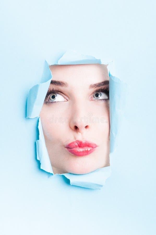 Γυναίκα που παρουσιάζει προκλητικά κόκκινα χείλια μέσω του αποκόπτω? χαρτονιού στοκ φωτογραφίες με δικαίωμα ελεύθερης χρήσης