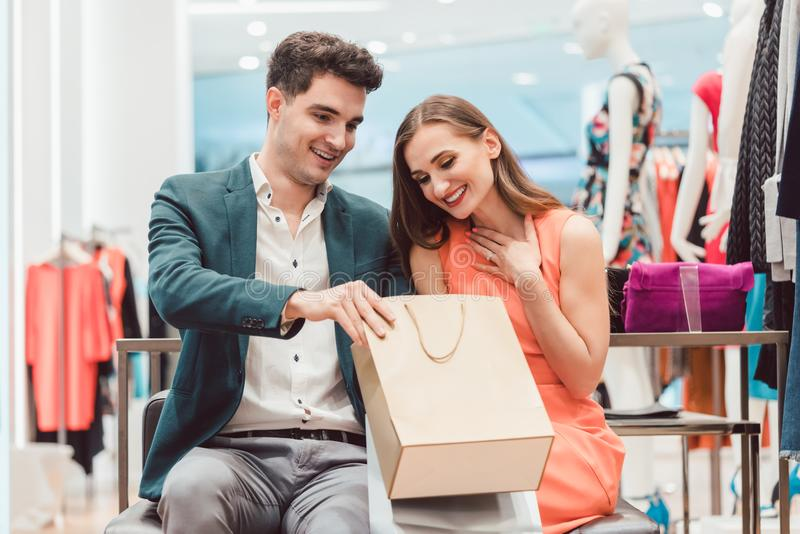 Γυναίκα που παρουσιάζει στον άνδρα της τι αγόρασε μέσα το κατάστημα μόδας στοκ φωτογραφίες