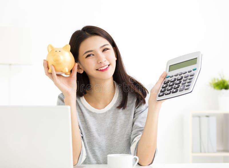 Γυναίκα που παρουσιάζει τον υπολογιστή και Piggybank στοκ φωτογραφία
