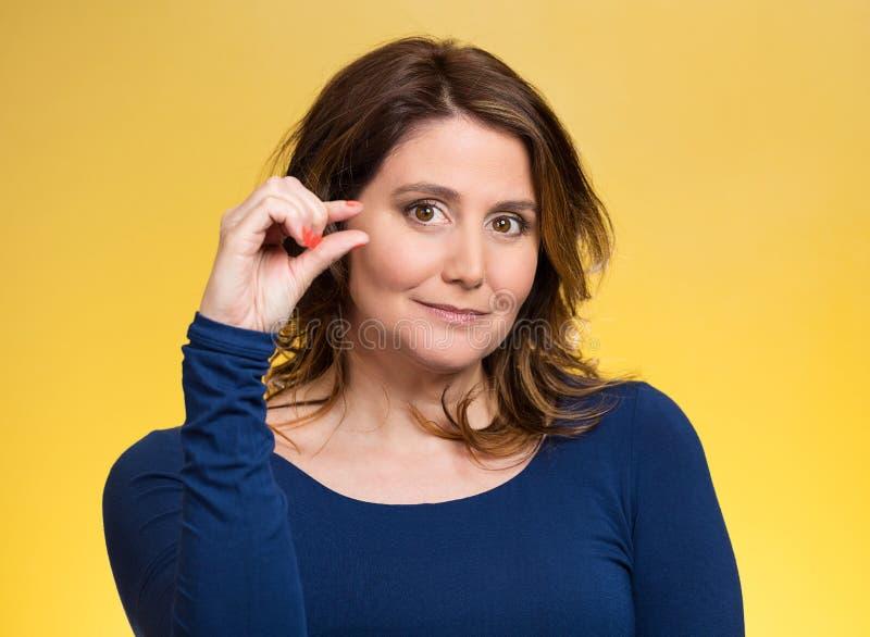 Γυναίκα, που παρουσιάζει χειρονομία μικρού ποσού με τα χέρια στοκ φωτογραφία