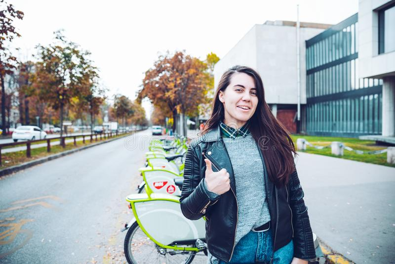 Γυναίκα που παρουσιάζει όπως την κοντινή υπηρεσία ποδηλάτων μισθώματος στοκ φωτογραφία με δικαίωμα ελεύθερης χρήσης