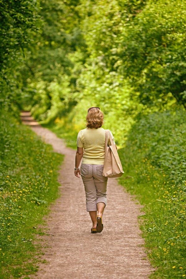 Γυναίκα που περπατά κάτω από ένα μονοπάτι μια ηλιόλουστη ημέρα στοκ φωτογραφία με δικαίωμα ελεύθερης χρήσης