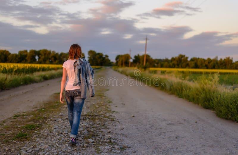 Γυναίκα που περπατά κάτω από μια εθνική οδό στοκ εικόνες