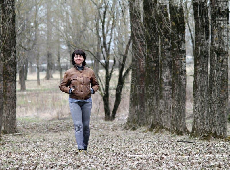 Γυναίκα που περπατά κάτω από την αλέα στοκ φωτογραφία