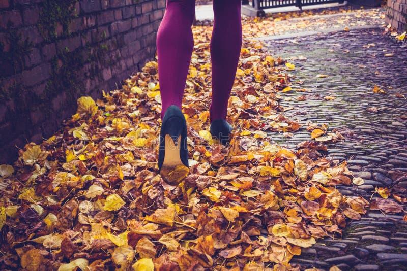 Γυναίκα που περπατά μέσω των φύλλων στοκ φωτογραφίες