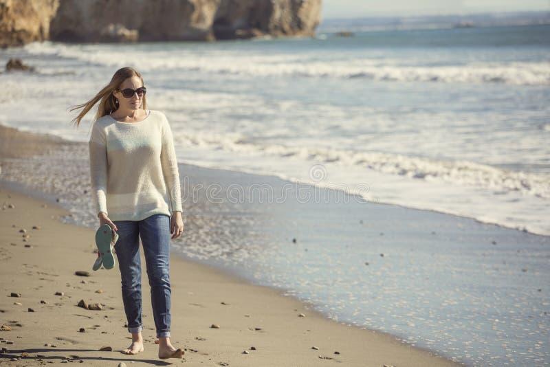 Γυναίκα που περπατά μόνο κατά μήκος μιας ειρηνικής παραλίας που σκέφτεται και που συλλογίζεται στοκ φωτογραφία