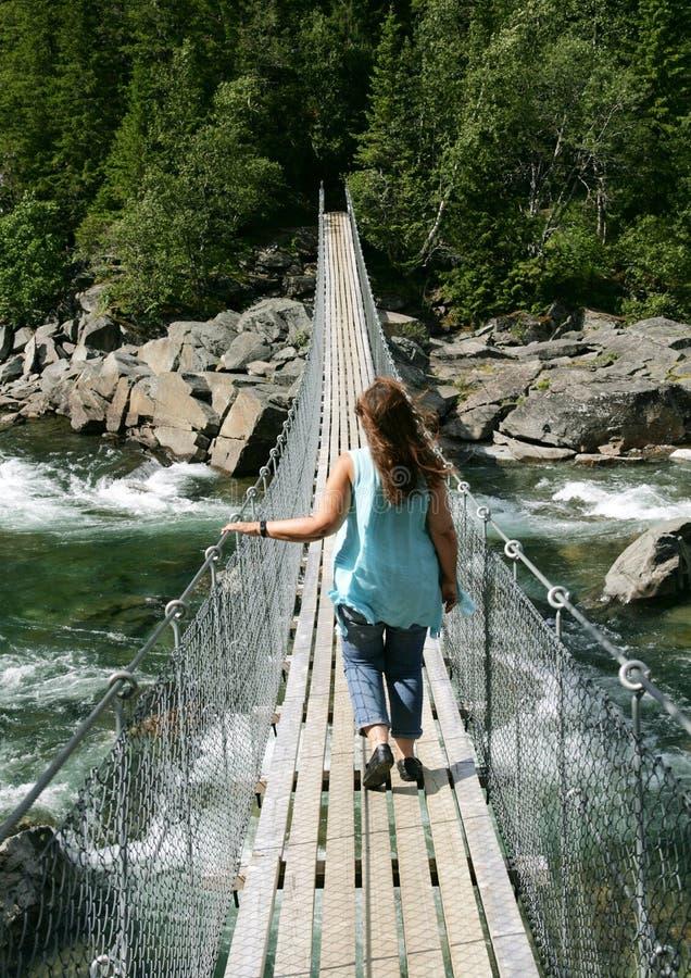 Γυναίκα που περπατά πέρα από μια γέφυρα αναστολής στοκ φωτογραφίες
