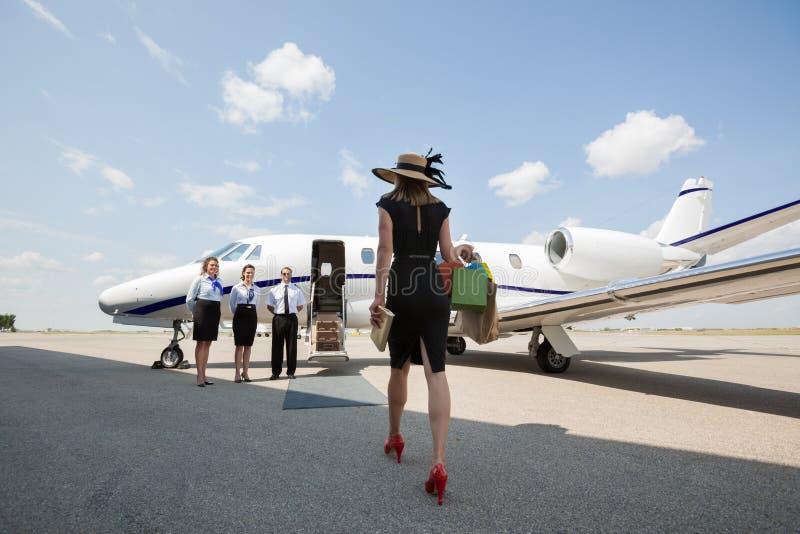 Γυναίκα που περπατά προς το ιδιωτικό αεριωθούμενο αεροπλάνο στον αερολιμένα στοκ εικόνα με δικαίωμα ελεύθερης χρήσης