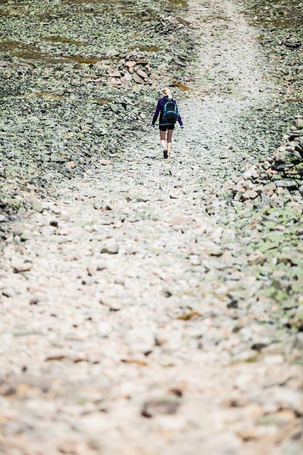 Γυναίκα που περπατά σε μια δύσκολη πορεία πεζοπορίας στοκ εικόνα με δικαίωμα ελεύθερης χρήσης