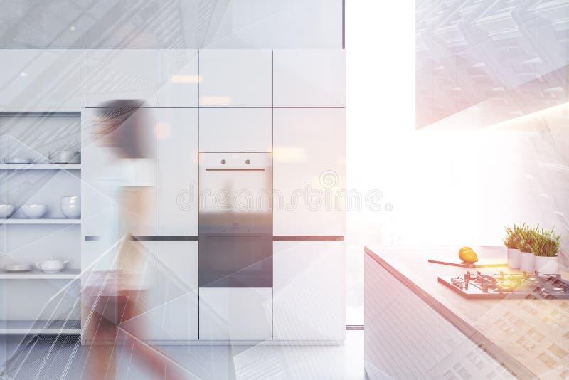 Γυναίκα που περπατά στην άσπρη κουζίνα με τα ντουλάπια στοκ φωτογραφίες