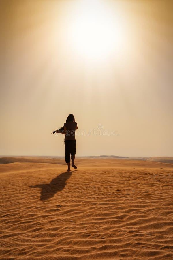 Γυναίκα που περπατά στην καυτή έρημο στοκ εικόνες