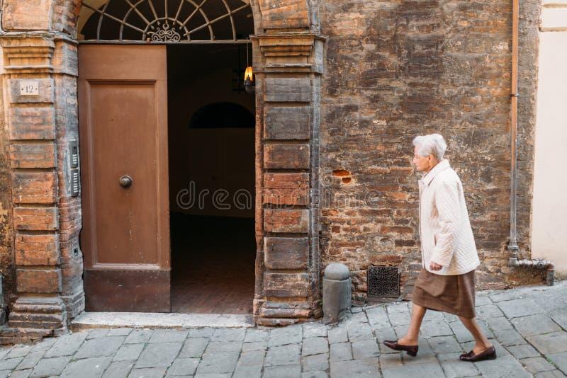 Γυναίκα που περπατά στην οδό από το παλαιό κτήριο στη Σιένα στοκ εικόνα