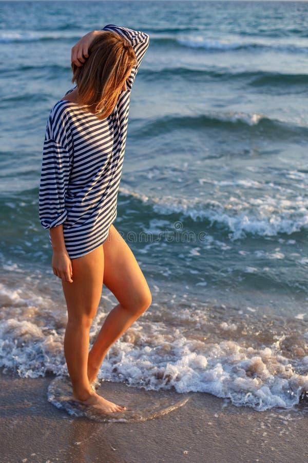 Γυναίκα που περπατά στην παραλία στο χρόνο ηλιοβασιλέματος της χαλάρωσης στοκ εικόνα με δικαίωμα ελεύθερης χρήσης