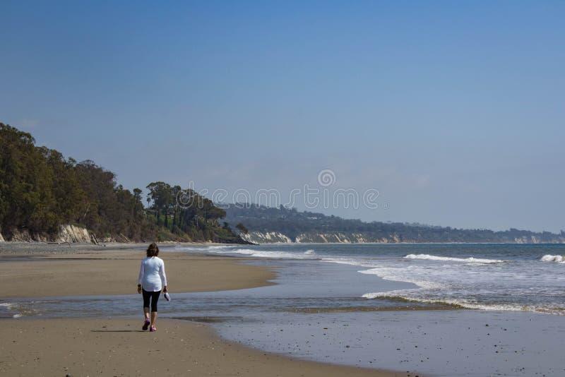 Γυναίκα που περπατά στην παραλία στοκ φωτογραφίες με δικαίωμα ελεύθερης χρήσης