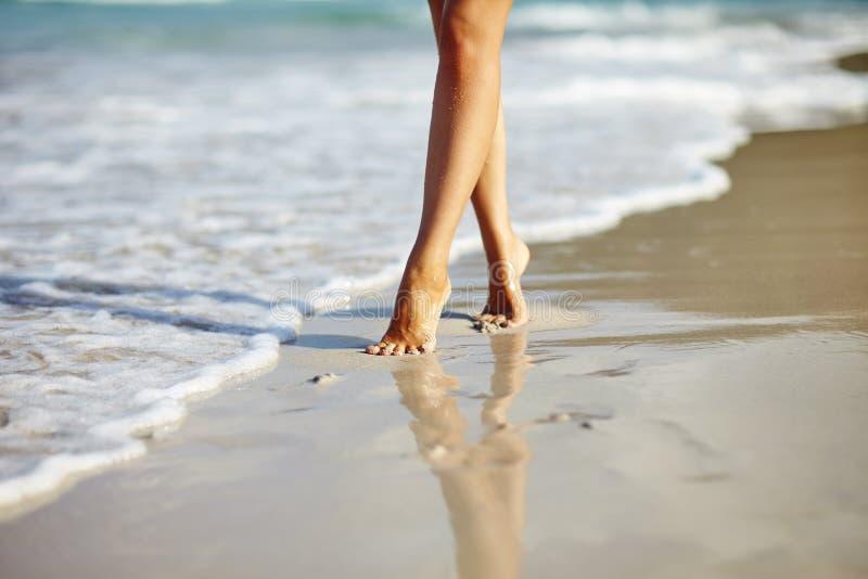 Γυναίκα που περπατά στην παραλία στοκ εικόνα με δικαίωμα ελεύθερης χρήσης