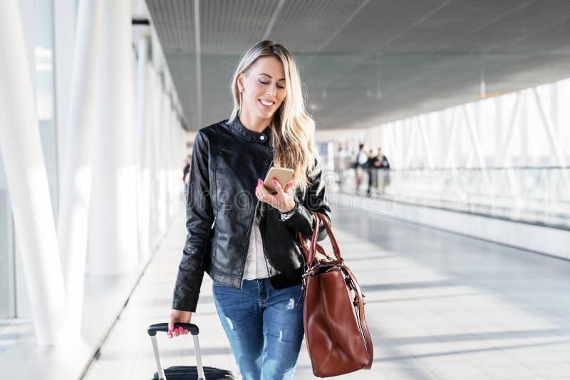 Γυναίκα που περπατά στον αερολιμένα και που εξετάζει το κινητό τηλέφωνο στοκ εικόνα