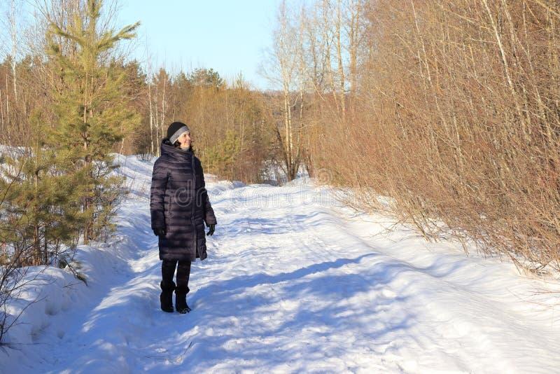 Γυναίκα που περπατά στο χιόνι στοκ φωτογραφία