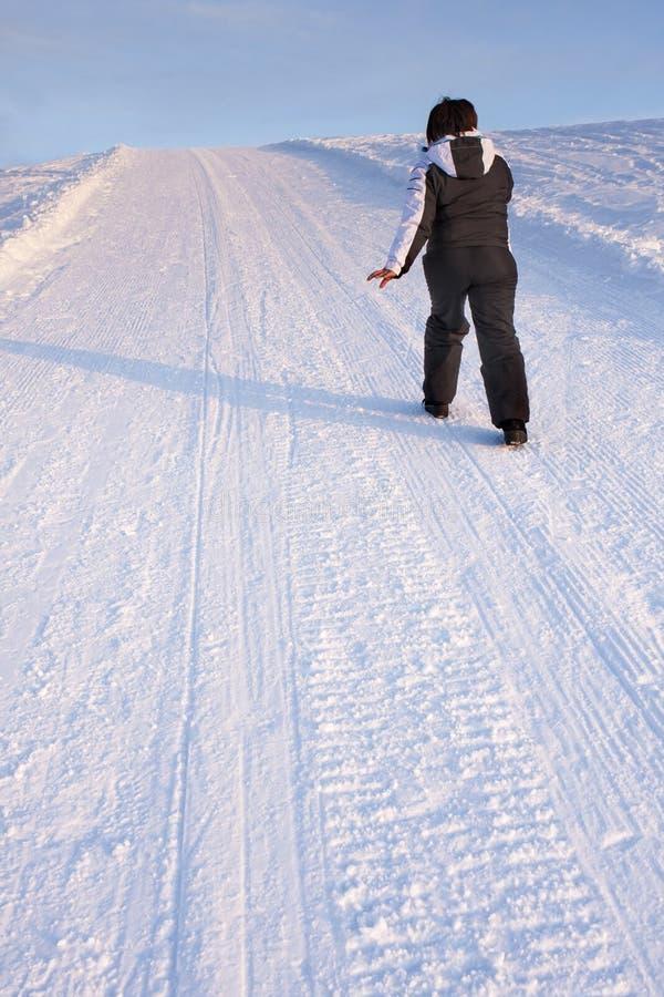 Γυναίκα που περπατά την ανηφορική διαδρομή βουνών χιονιού στοκ φωτογραφία με δικαίωμα ελεύθερης χρήσης
