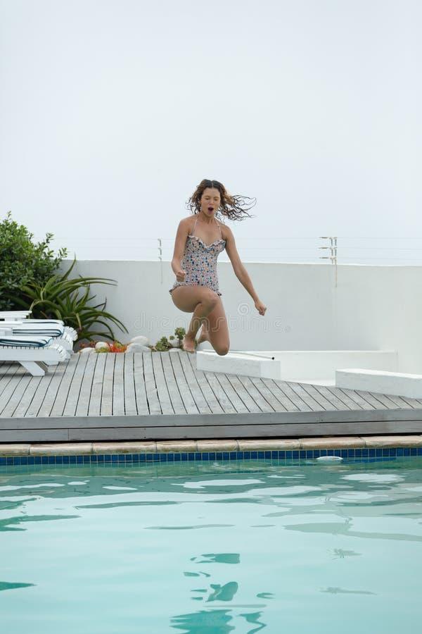 Γυναίκα που πηδά στην πισίνα στο κατώφλι του σπιτιού στοκ εικόνα