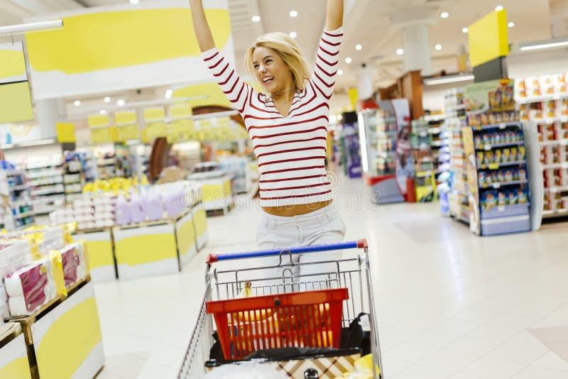 Γυναίκα που πηδά από τη χαρά στην υπεραγορά στοκ φωτογραφία
