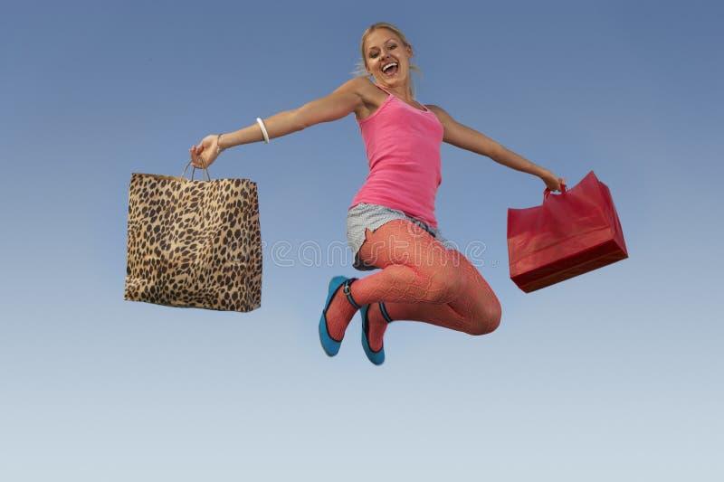 Γυναίκα που πηδά με τις τσάντες ενάντια στο μπλε ουρανό στοκ εικόνες
