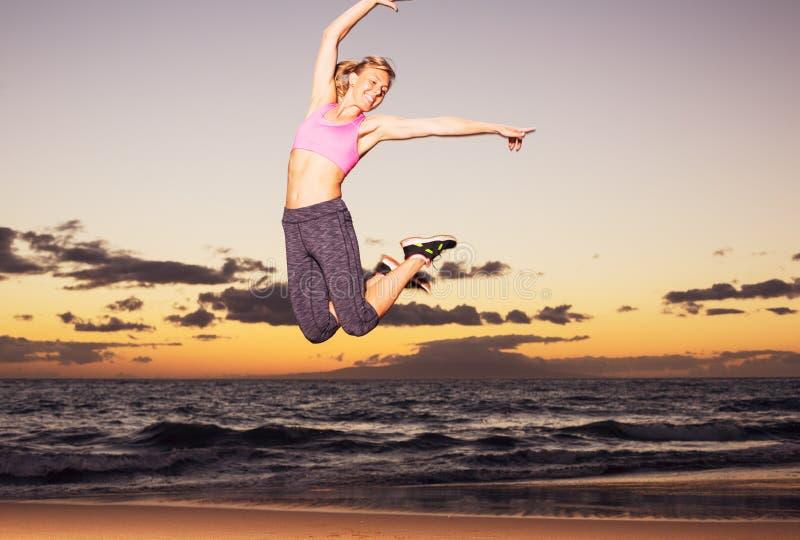 Γυναίκα που πηδά στην παραλία στο ηλιοβασίλεμα στοκ φωτογραφία
