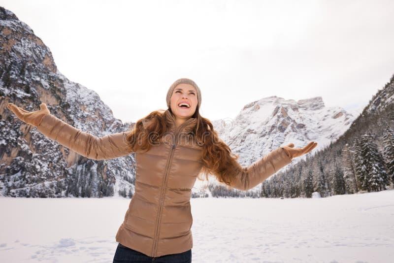 Γυναίκα που πιάνει snowflakes υπαίθρια μεταξύ των χιονοσκεπών βουνών στοκ εικόνα