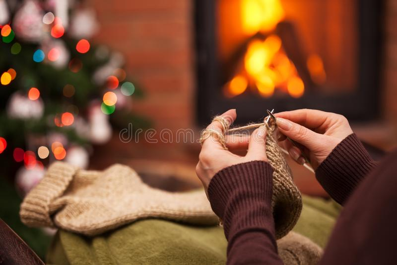 Γυναίκα που πλέκει τις μάλλινες κάλτσες που κάθονται από το χριστουγεννιάτικο δέντρο και την εστία το βράδυ περιόδου διακοπών στοκ εικόνα με δικαίωμα ελεύθερης χρήσης