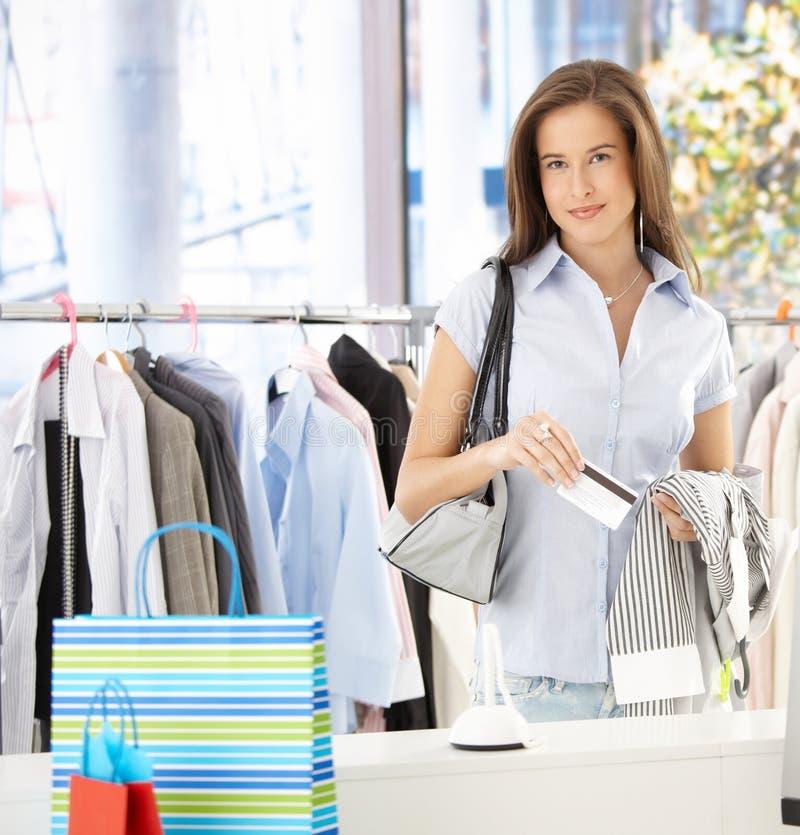 Γυναίκα που πληρώνει στο κατάστημα ενδυμάτων στοκ φωτογραφία με δικαίωμα ελεύθερης χρήσης