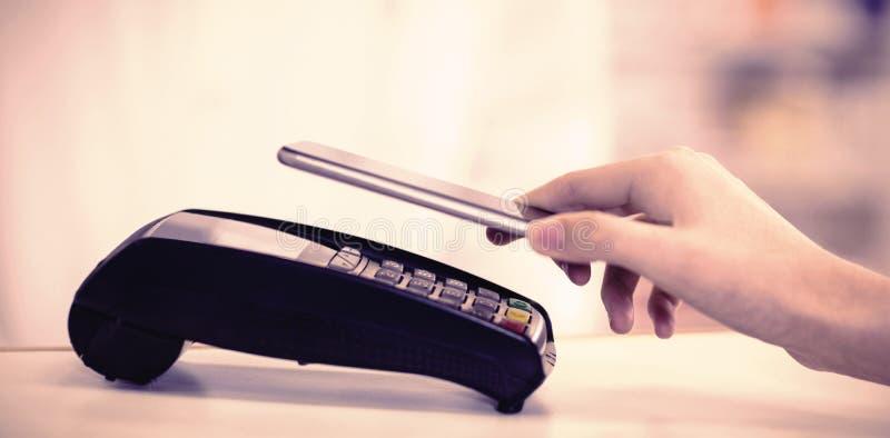 Γυναίκα που πληρώνει το λογαριασμό μέσω του smartphone που χρησιμοποιεί nfc την τεχνολογία στοκ εικόνες