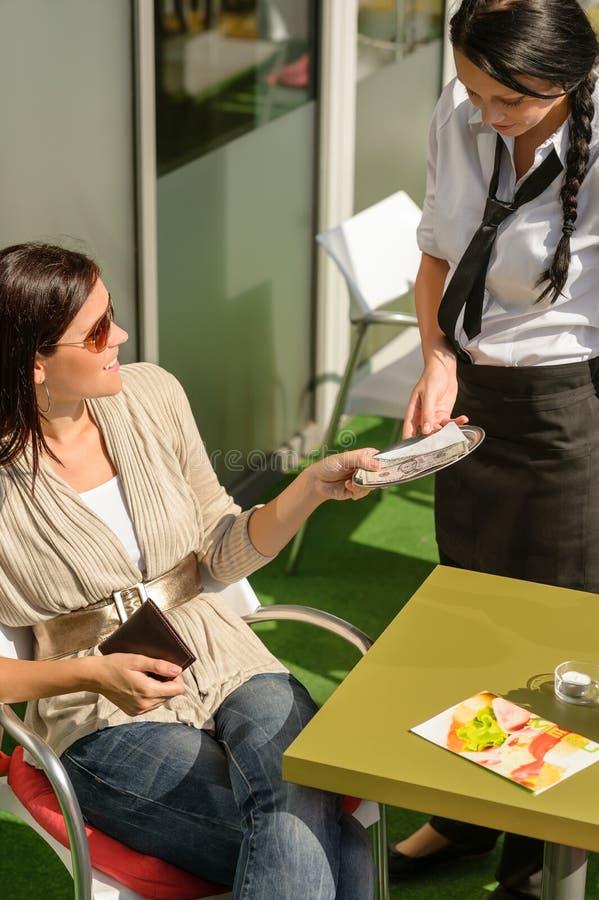 Γυναίκα που πληρώνει το λογαριασμό στο εστιατόριο καφέδων σερβιτορών στοκ φωτογραφία