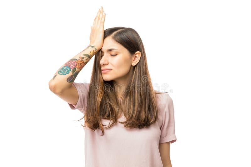Γυναίκα που πραγματοποιεί το λάθος και που κρατά το χέρι στο κεφάλι στοκ εικόνες