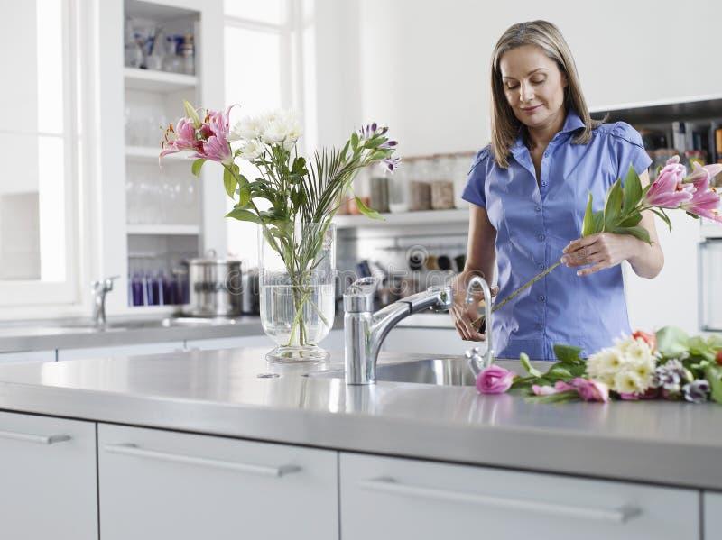 Γυναίκα που προετοιμάζει τα λουλούδια για το βάζο στο νεροχύτη κουζινών στοκ εικόνες