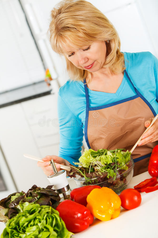 Γυναίκα που προετοιμάζει τη σαλάτα στην κουζίνα. στοκ εικόνες