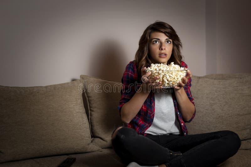 Γυναίκα που προσέχει μια ταινία τρόμου στη TV στοκ εικόνες με δικαίωμα ελεύθερης χρήσης