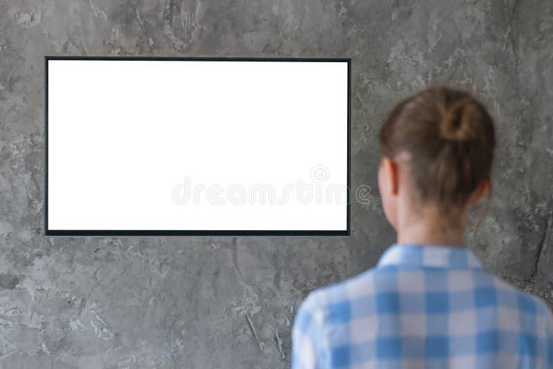 Γυναίκα που προσέχει την επίπεδη έξυπνη οδηγημένη TV με την άσπρη κενή ed TV οθόνης με την άσπρη κενή οθόνη - έννοια προτύπων στοκ φωτογραφίες