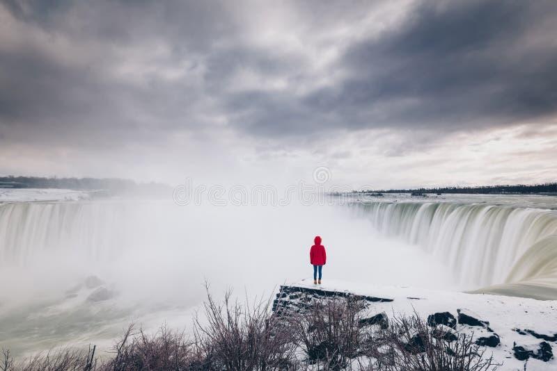 Γυναίκα που προσέχει τις πτώσεις Niagara από μια χιονώδη προεξοχή στοκ φωτογραφίες