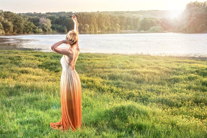 Γυναίκα που προσέχει το ηλιοβασίλεμα σε ένα μακρύ γοητευτικό φόρεμα κορίτσι καλό Όμορφη άποψη τοπίων, πυροβολισμός από την πλάτη στοκ φωτογραφίες