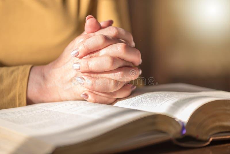 Γυναίκα που προσεύχεται με τα χέρια της πέρα από τη Βίβλο, σκληρό φως στοκ εικόνα με δικαίωμα ελεύθερης χρήσης