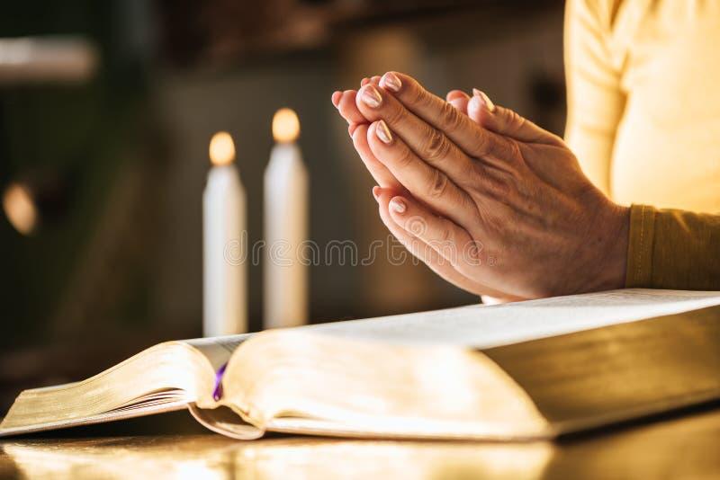 Γυναίκα που προσεύχεται με τα χέρια της πέρα από τη Βίβλο, σκληρό φως στοκ φωτογραφίες