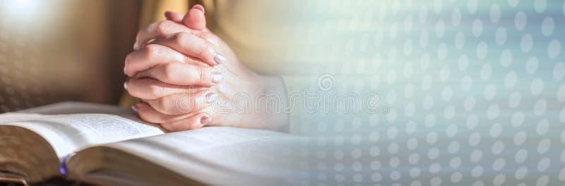 Γυναίκα που προσεύχεται με τα χέρια της πέρα από τη Βίβλο, σκληρό φως  πανοραμικό έμβλημα στοκ φωτογραφίες