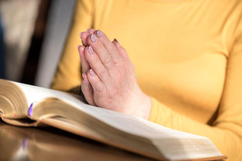 Γυναίκα που προσεύχεται με τα χέρια της πέρα από τη Βίβλο στοκ φωτογραφία