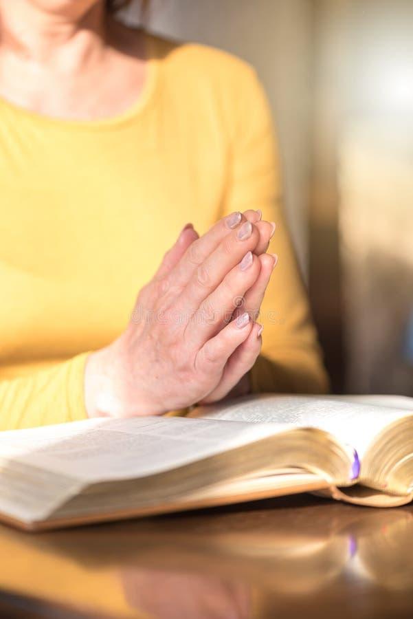 Γυναίκα που προσεύχεται με τα χέρια της πέρα από τη Βίβλο στοκ εικόνες με δικαίωμα ελεύθερης χρήσης