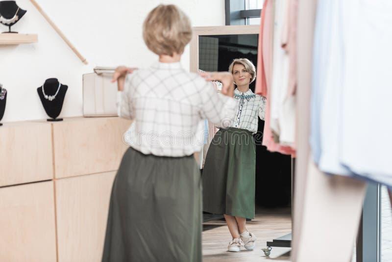Γυναίκα που προσπαθεί σε ένα περιδέραιο στο κατάστημα στο μέτωπο στοκ φωτογραφία