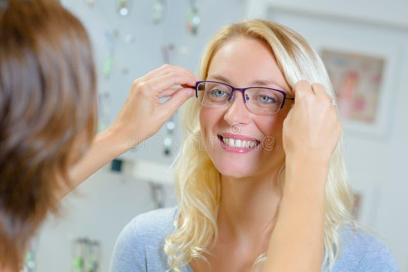 Γυναίκα που προσπαθεί στα γυαλιά στο οπτικό κατάστημα στοκ φωτογραφίες με δικαίωμα ελεύθερης χρήσης