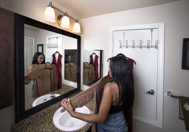 Γυναίκα που προσπαθεί στα ενδύματα που εξετάζουν τον καθρέφτη στο λουτρό στοκ εικόνα